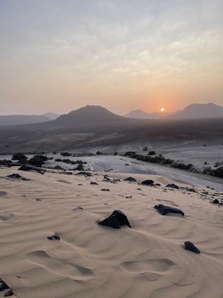 Sunset over the sandy desert landscape in Namibia.