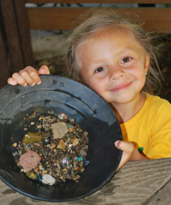 Young girl shows off the rocks and gems in her mining pan.